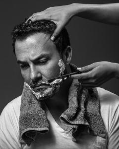 Acquiescence woman shaving man with straight razor